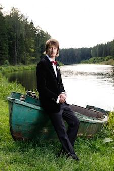 Bello giovane sposo che si siede sulla barca