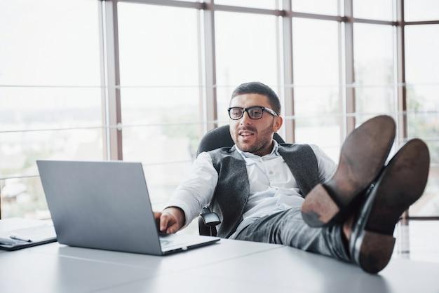 Bello giovane uomo d'affari con i vetri che tengono le sue gambe sul tavolo che esamina un computer portatile nell'ufficio