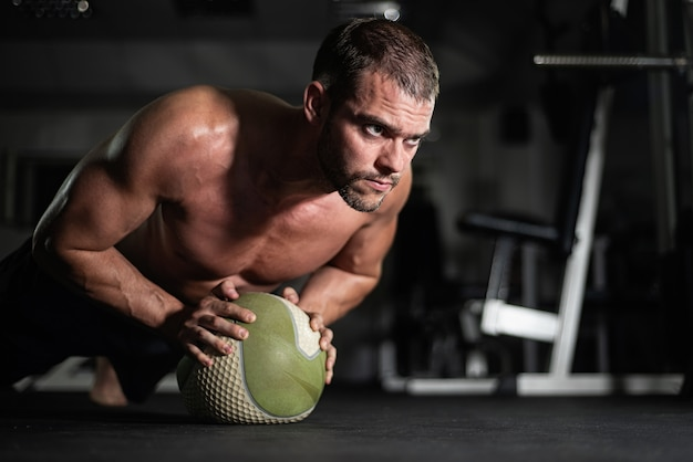 Bello giovane uomo muscolare che fa ginnastica in palestra con la palla