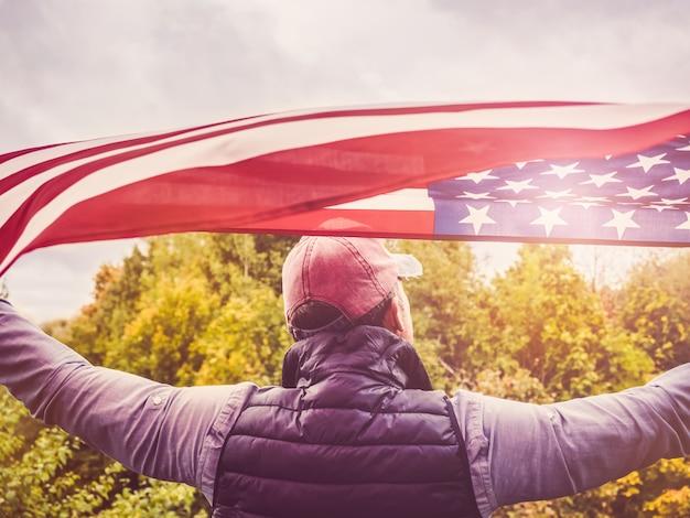 Bello, giovane uomo sventolando una bandiera americana