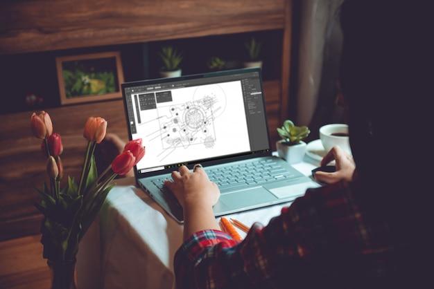 Bello grafico asiatico della giovane donna che lavora dalla casa sul computer portatile mentre sedendosi al salone del condominio