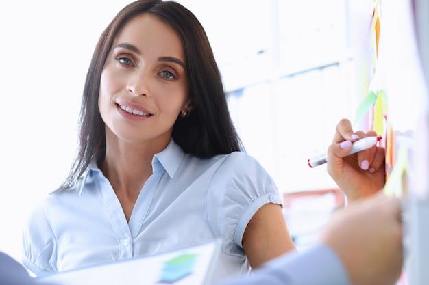 Bello impiegato femminile che disegna qualcosa sulla lavagna durante la conversazione di affari