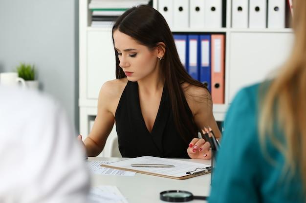 Bello impiegato femminile che lavora con i documenti finanziari
