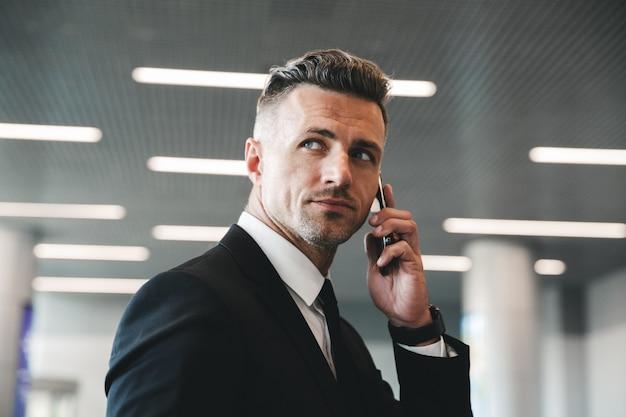 Bello imprenditore maturo parlando al telefono cellulare