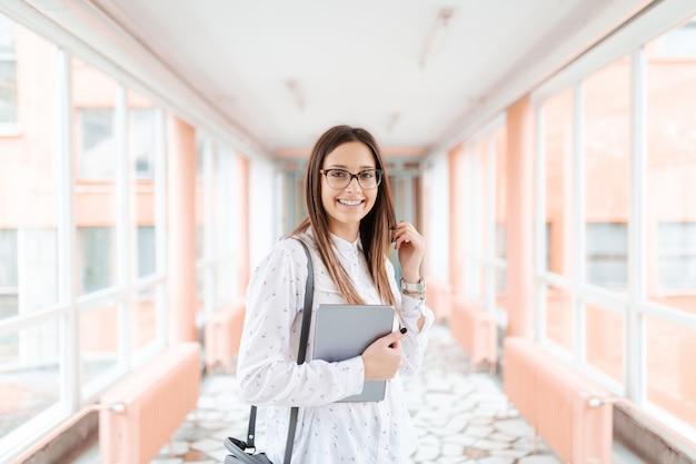Bello insegnante femminile sorridente con la compressa e la borsa sulla spalla che va classificare.