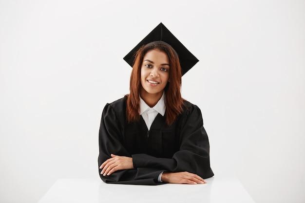 Bello laureato femminile che sorride esaminando macchina fotografica che si siede sopra la superficie bianca