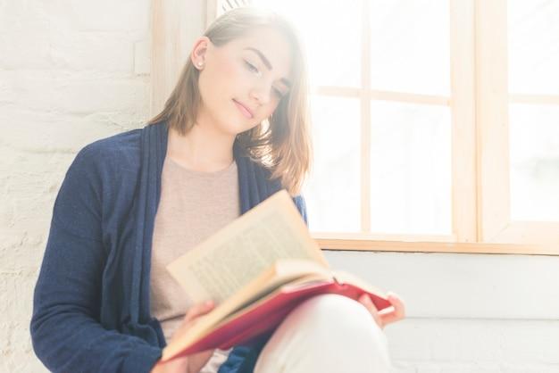 Bello libro di lettura della giovane donna a casa