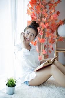 Bello libro di lettura della giovane donna vicino alla finestra a casa