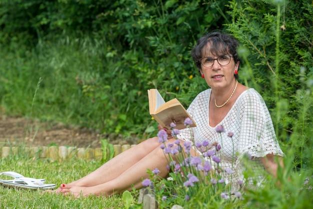 Bello libro di lettura senior della donna nel giardino