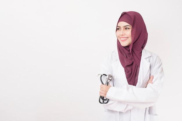 Bello medico della donna con il ritratto di hijab sulla parete bianca