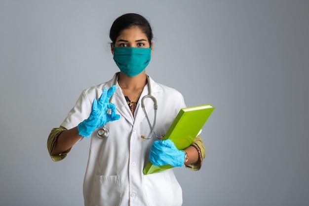 Bello medico della giovane donna che posa con la perizia medica o il libro e che mostra segno.