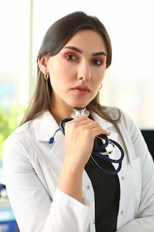 Bello medico femminile sorridente nel ritratto del posto di lavoro