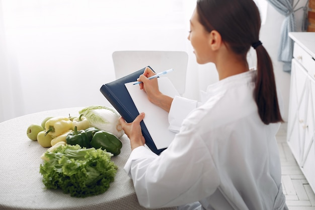 Bello medico in una cucina con verdure