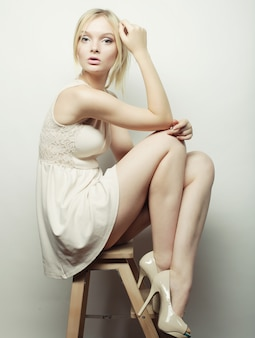 Bello modello biondo che si siede su uno sgabello
