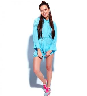 Bello modello caucasico sorridente della donna del brunette in vestito alla moda da estate blu luminosa isolato su priorità bassa bianca. lunghezza intera