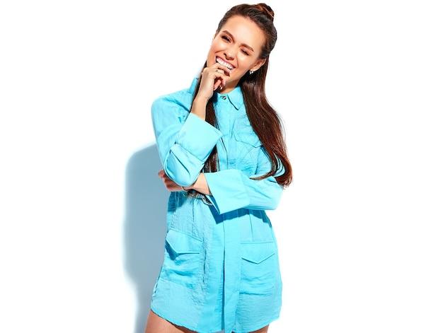 Bello modello caucasico sorridente della donna del brunette in vestito alla moda da estate blu luminosa isolato su priorità bassa bianca. mordendosi il dito