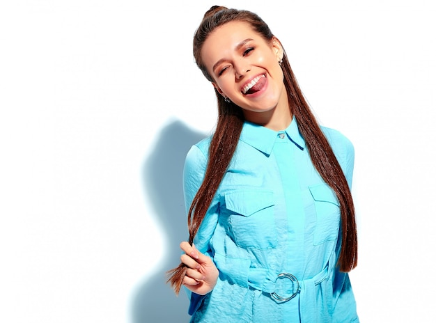 Bello modello caucasico sorridente della donna del brunette in vestito alla moda da estate blu luminosa isolato su priorità bassa bianca. mostrando la sua lingua