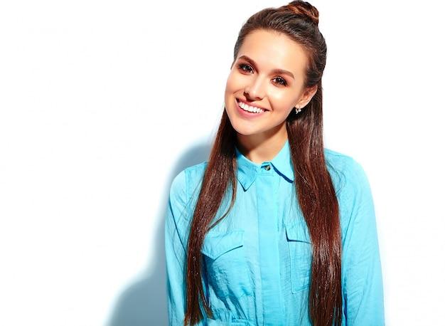 Bello modello caucasico sorridente della donna del brunette in vestito alla moda da estate blu luminosa isolato su priorità bassa bianca
