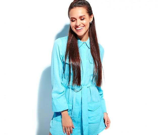Bello modello caucasico sorridente della donna del brunette in vestito alla moda da estate blu luminosa
