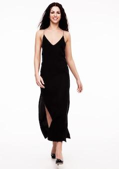 Bello modello di moda sexy che porta vestito nero che cammina sulla passerella su bianco