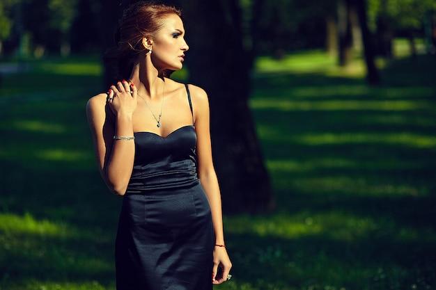 Bello modello sexy alla moda della giovane donna in vestito nero che posa nel parco