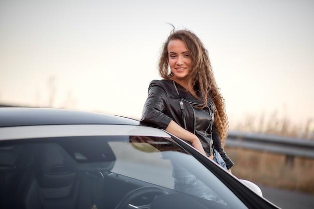 Bello modello sexy che posa in una giacca di pelle e con capelli ricci vicino all'automobile al tramonto