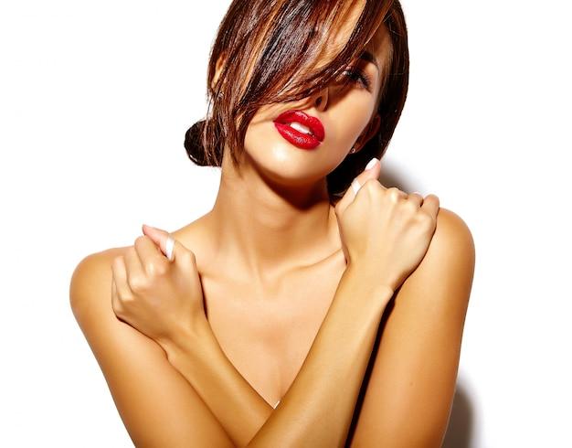 Bello modello sexy preso il sole caldo della donna con le spalle nude e le labbra rosse su fondo bianco