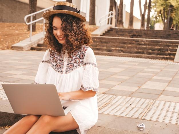 Bello modello sorridente con l'acconciatura dei riccioli di afro in vestito e cappello bianchi dai pantaloni a vita bassa di estate.