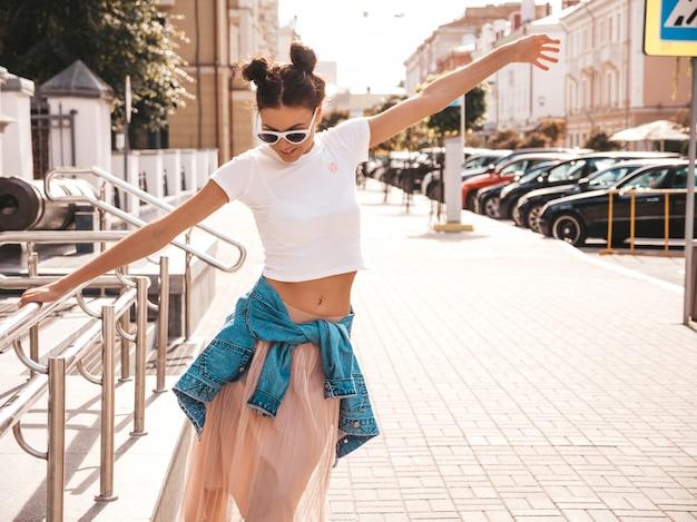 Bello modello sorridente con l'acconciatura di corna vestita in abiti jeans giacca estiva pantaloni a vita bassa ragazza spensierata sexy in posa in strada. donna divertente e positiva di tendenza divertendosi in occhiali da sole