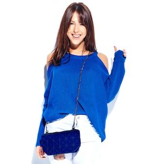 Bello modello sorridente della donna castana dei pantaloni a vita bassa in maglione alla moda casuale e borsa blu isolati su fondo bianco che mostra il segno di pace