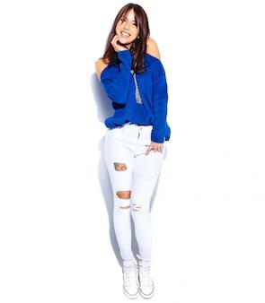 Bello modello sorridente della donna castana dei pantaloni a vita bassa in maglione blu di estate alla moda casuale isolato su fondo bianco lunghezza completa