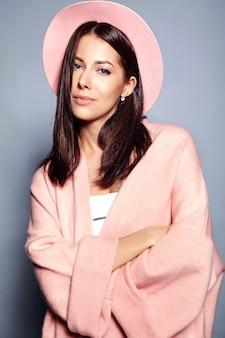 Bello modello sorridente della donna castana dei pantaloni a vita bassa in soprabito rosa alla moda e cappello variopinto che posano sul gray