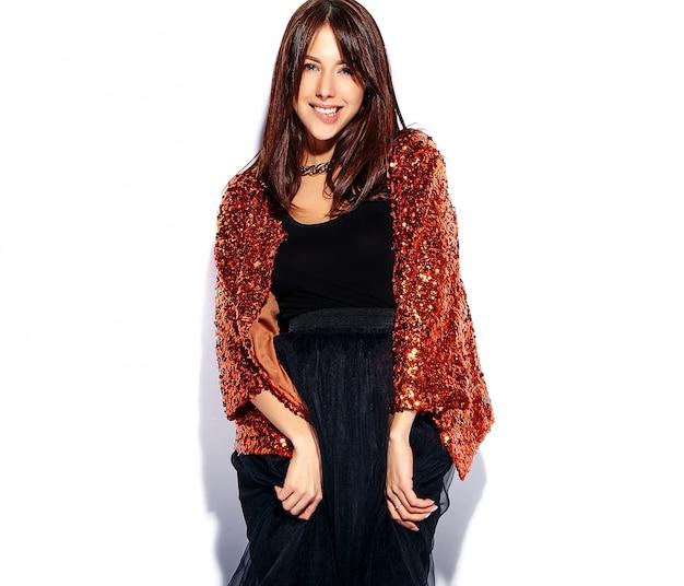 Bello modello sorridente della donna del brunette dei pantaloni a vita bassa in vestiti alla moda moderni luminosi di estate isolati. mordendosi il labbro