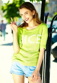 Bello modello sorridente sexy alla moda divertente della giovane donna in panno giallo luminoso dei pantaloni a vita bassa di estate nella via