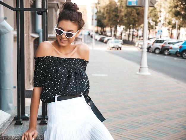 Bello modello sorridente vestito in eleganti abiti estivi. ragazza spensierata sexy che si siede in strada. donna di affari moderna alla moda in divertimento degli occhiali da sole