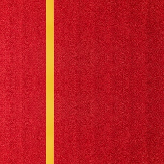 Bello nastro dorato del raso lucido sul fondo variopinto della carta o del regalo di scintillio di rosso