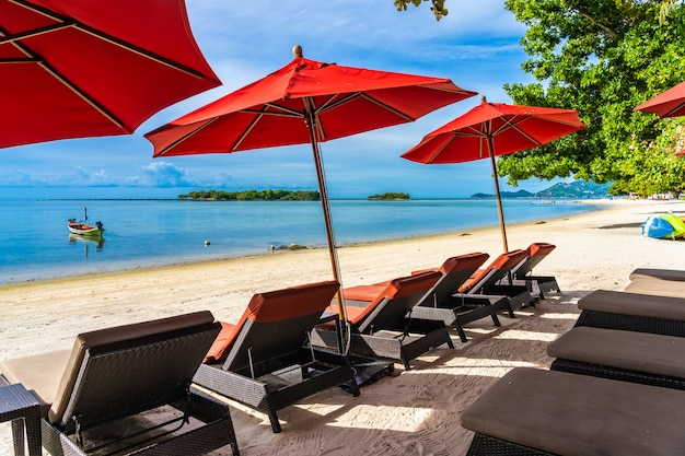Bello oceano tropicale all'aperto del mare della spiaggia con la sedia dell'ombrello e la piattaforma del salotto intorno là sul cielo blu bianco della nuvola