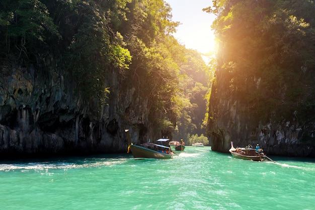 Bello paesaggio della montagna delle rocce e del mare cristallino con la barca del longtail a phuket, tailandia.
