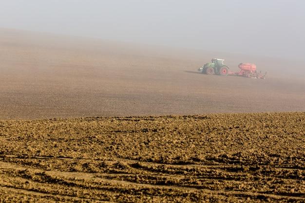 Bello paesaggio nebbioso nebbioso di autunno con il trattore funzionante nella moravia del sud, repubblica ceca.
