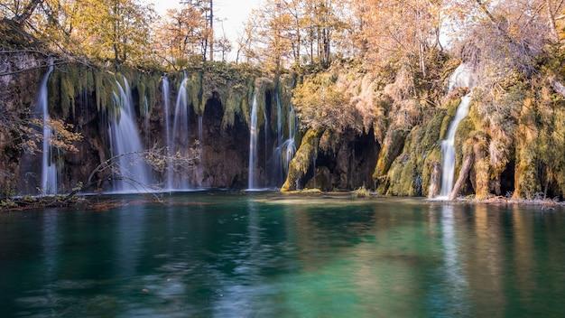 Bello paesaggio sparato di un lago scenico con le cascate che sfociano in plitvice, croazia