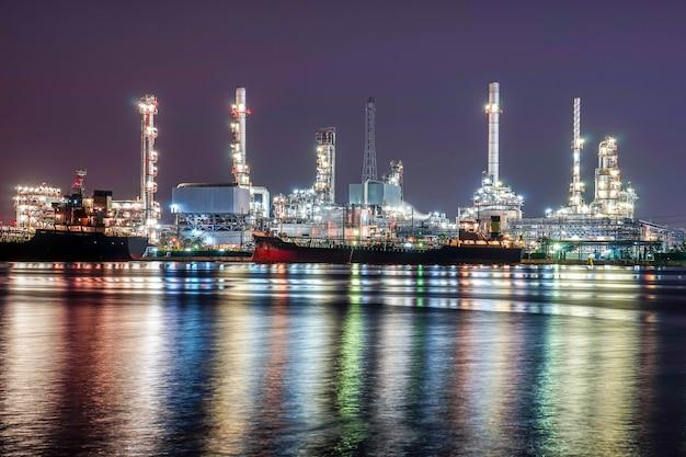Bello paesaggio urbano della pianta della fabbrica della raffineria di petrolio petrochimico di tramonto alla notte
