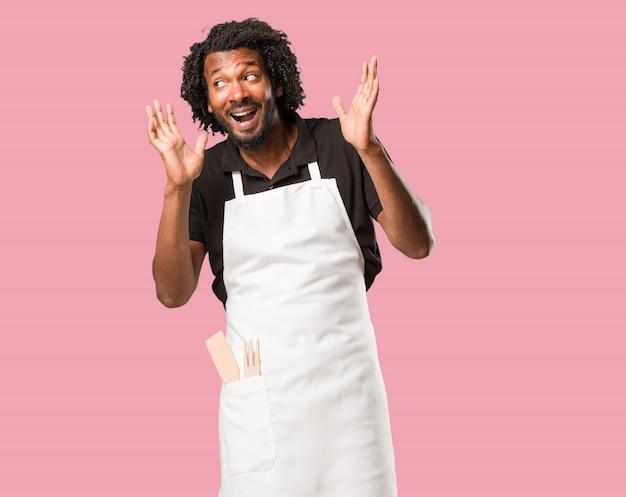 Bello panettiere afroamericano sorpreso e scioccato, guardando con gli occhi spalancati, eccitato da un'offerta o da un nuovo lavoro, vincere il concetto