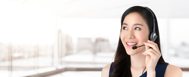 Bello personale asiatico di call center di servizio di assistenza al cliente che guarda per svuotare spazio