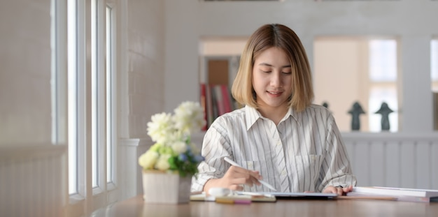 Bello progettista femminile che lavora alla compressa dello schermo in bianco nella sua area di lavoro