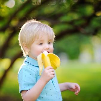 Bello ragazzino che mangia banana durante il picnic nel parco soleggiato di estate