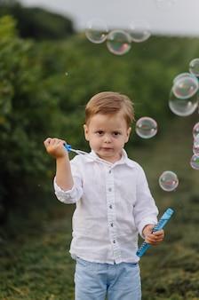 Bello ragazzo che gioca con le bolle il giorno soleggiato nel giardino.