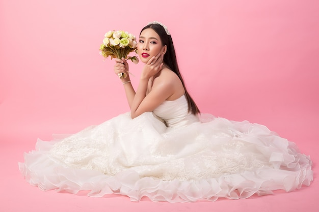 Bello ritratto asiatico della sposa in studio rosa