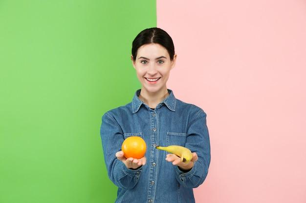 Bello ritratto del primo piano di giovane donna con i frutti.