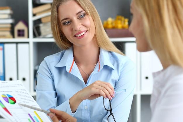 Bello ritratto della donna all'esame del posto di lavoro