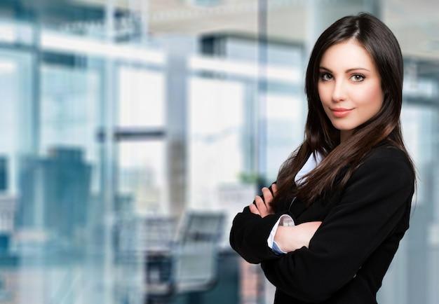 Bello ritratto della donna di affari in un ufficio moderno